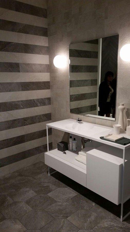 un bagno con delle piastrelle di color marrone e avorio