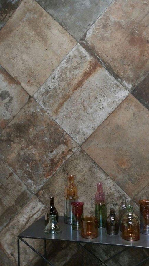 un muro con piastrelle a effetto roccia e davanti un tavolino con delle bottiglie colorate