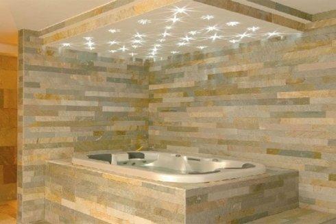 una vasca con idromassaggio  e i muri rivestiti con delle piastrelle