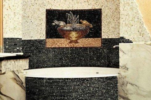 un bagno con una vasca e delle piastrelle di color nero e bianco