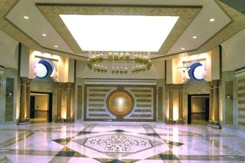 una hall con un pavimento in marmo bianco a disegni neri, delle colonne color beige e un lampadario al centro