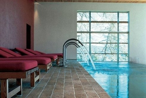 una piscina al coperto e accanto degli sdraio