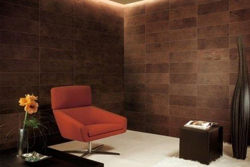una stanza con una poltrona di color arancione e due tavolini