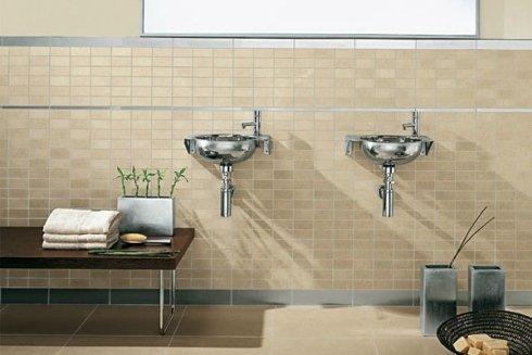 due lavandini a muro in acciaio e davanti un tavolino con degli asciugamani