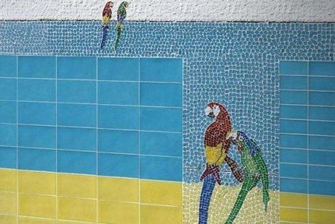 un muro con delle piastrelle di color azzurro e disegni dei pappagalli a mosaico