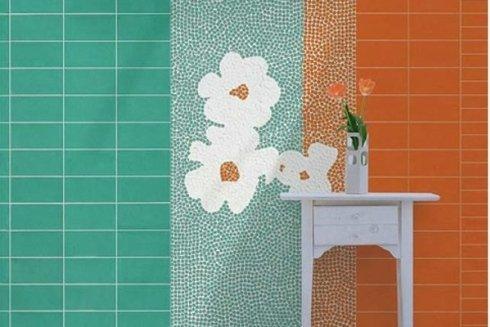 un muro con delle piastrelle i color turchese e arancione e disegni dei fiori di color bianco