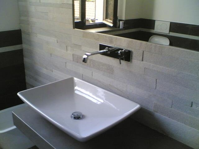 un bagno con un lavandino e uno specchio sopra