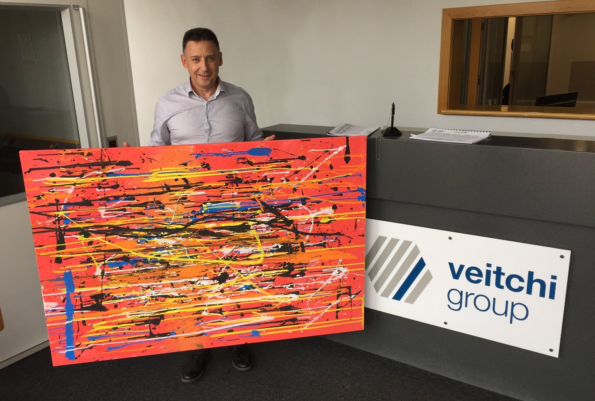 Veitchi Group directors standing next to the charity painting