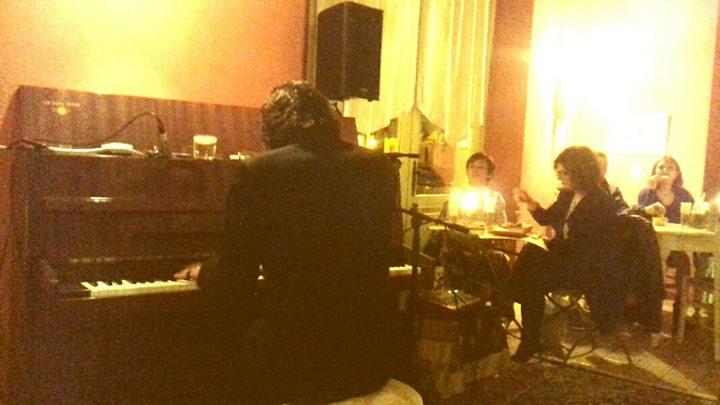 Pianista suona il piano mentre intrattiene la gente seduta ai tavoli