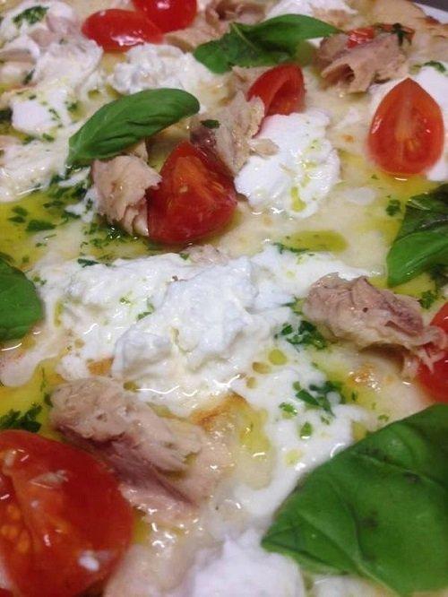 una pizza bianca con pomodoro, tonno mozzarella e basilico