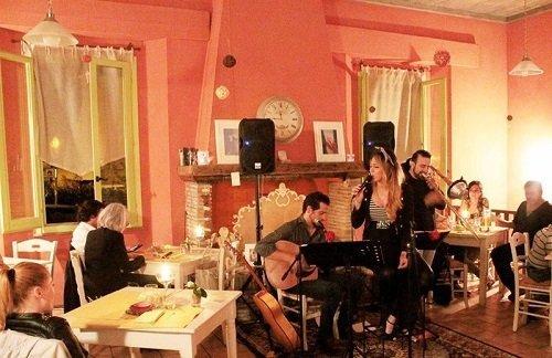 delle persone che suonano e cantano e altre sedute ai tavoli in un ristorante