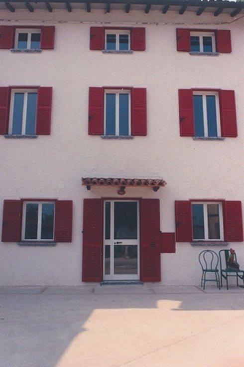 Facciata di un condominio con persiane rosse