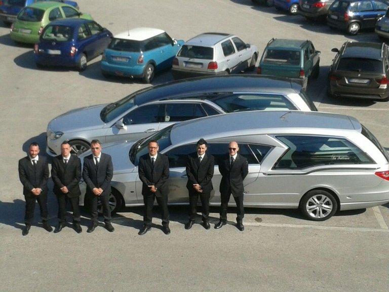 flotta di carri funebre con personale dell'agenzia
