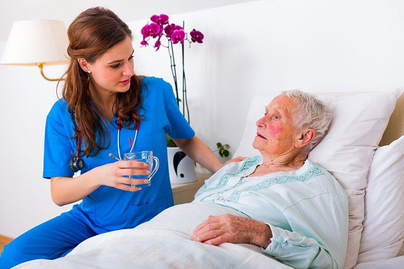 Infermiera curando teneramente a un anziano