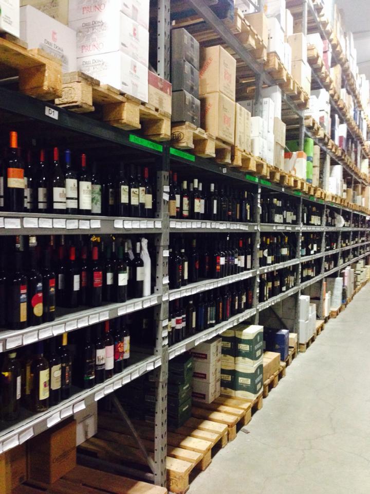 Degli scaffali con delle bottiglie di vino e dei bancali