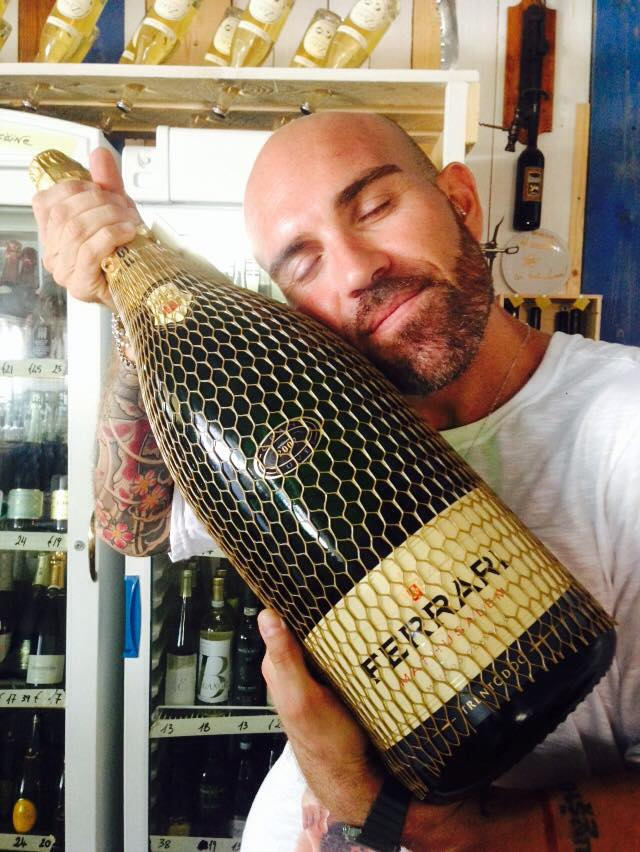 Un uomo che abbraccia una bottiglia di vino della marca ferrari