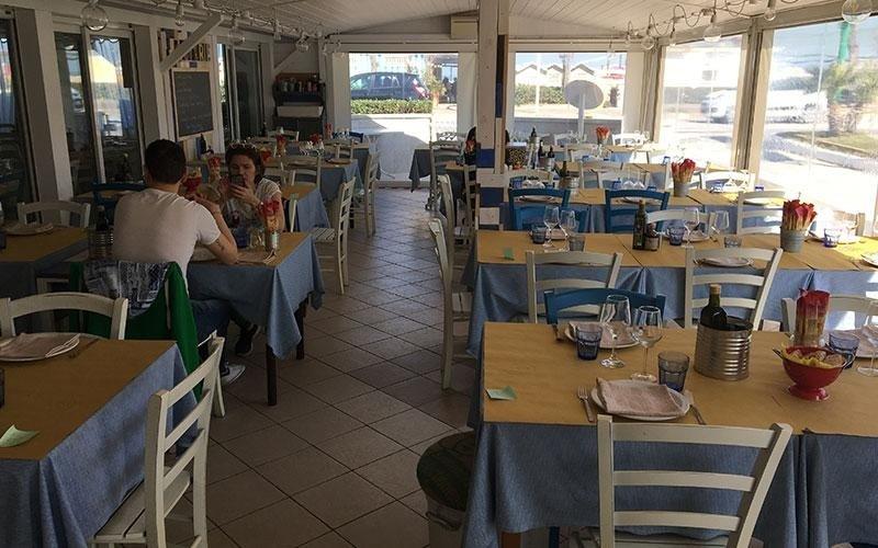 Dei tavoli apparecchiati con delle tovaglie di colore azzurro