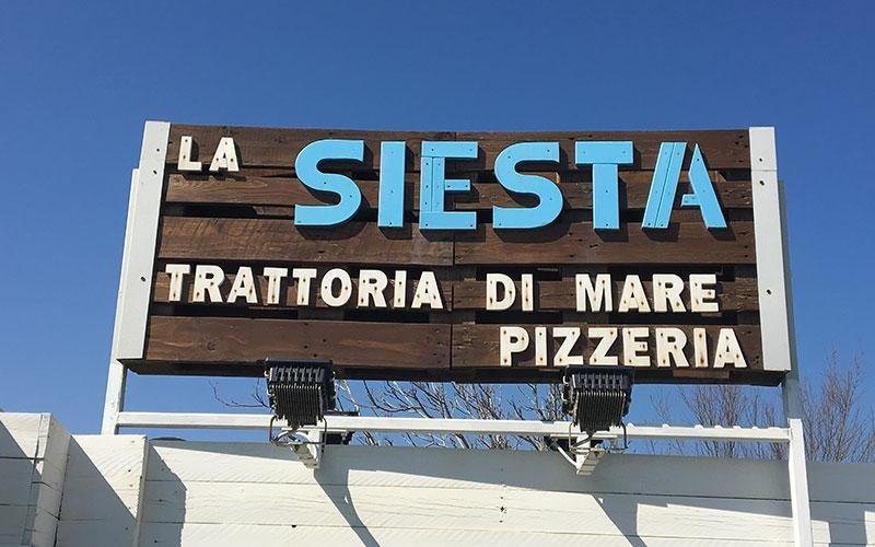 un cartello con scritto La Siesta Trattoria Di Mare PIzzeria