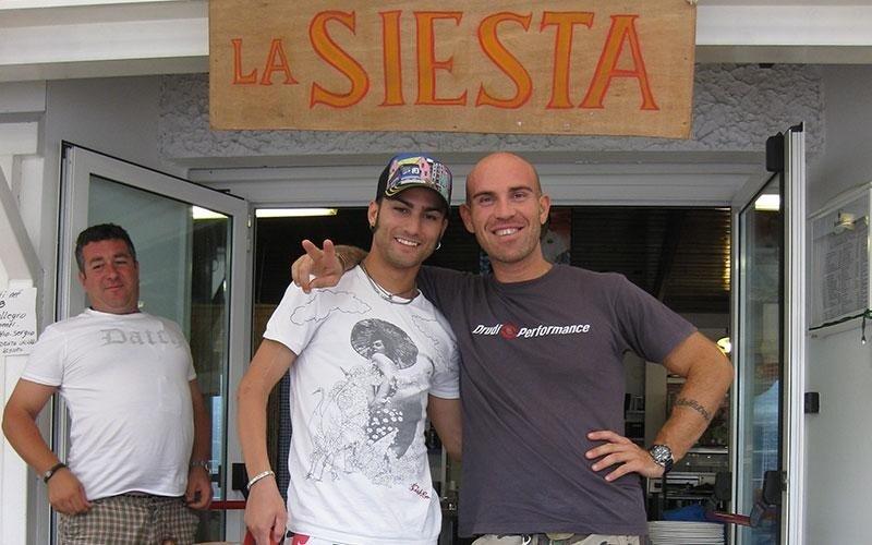 un ragazzo accanto a Mattia Pasini pilota di Moto Gp in posa per una foto