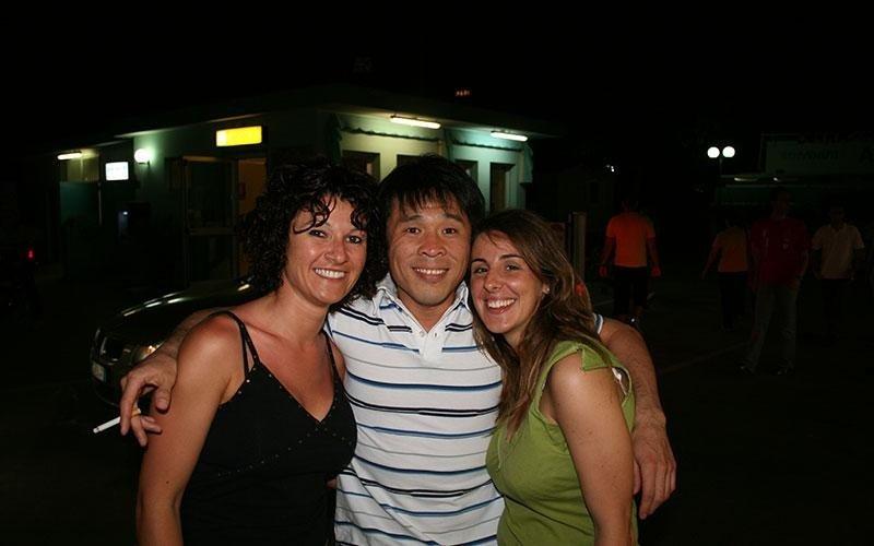 un ragazzo asiatico e accanto due ragazze in posa per una foto