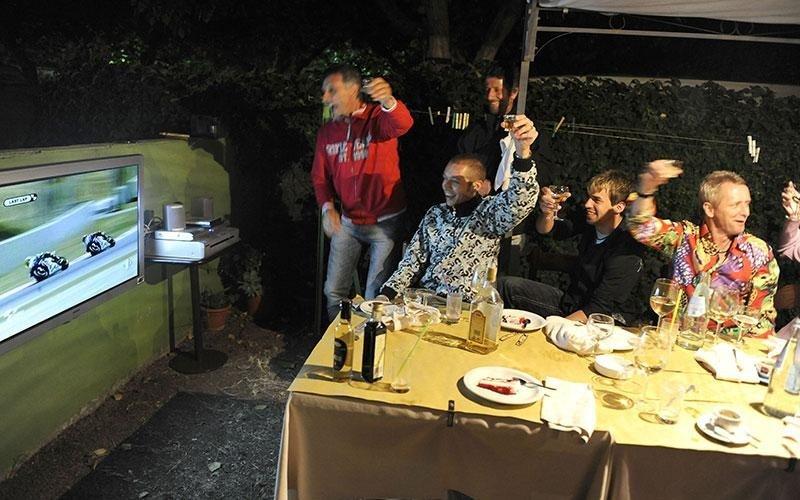 Valentino Rossi e altre persone a un tavolo che brindano mentre guardano una gara di Moto Gp
