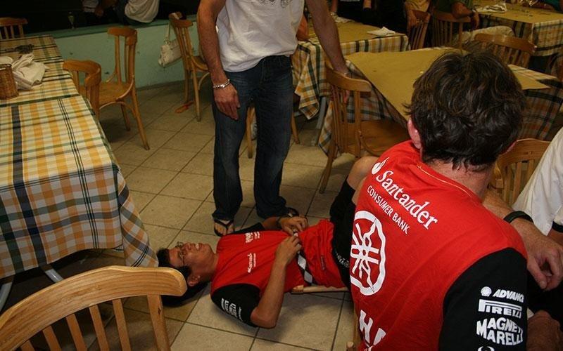 un ragazzo con una maglietta rossa sdraiato per terra in un ristorante