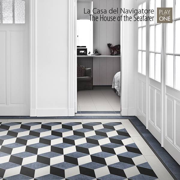 un ingresso con un pavimento con piastrelle a forme geometriche nere,bianche e grigie