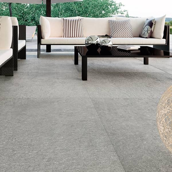 un pavimento grigio e vista di un tavolino in legno e un divano beige