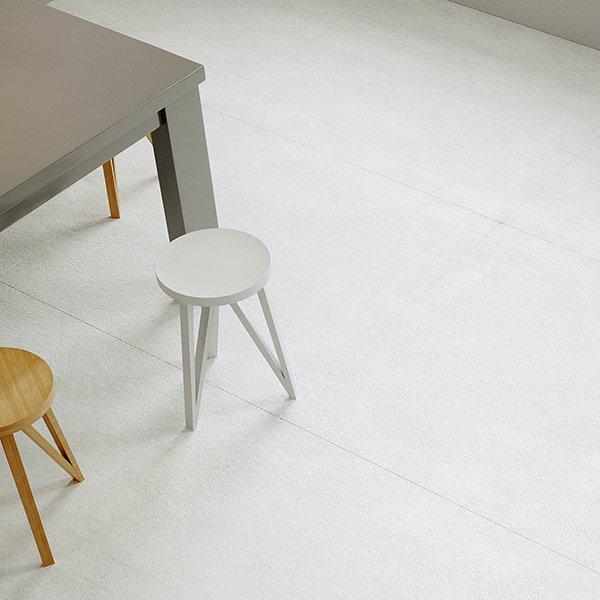 due sgabelli, un tavolo grigio e il pavimento con piastrelle bianche