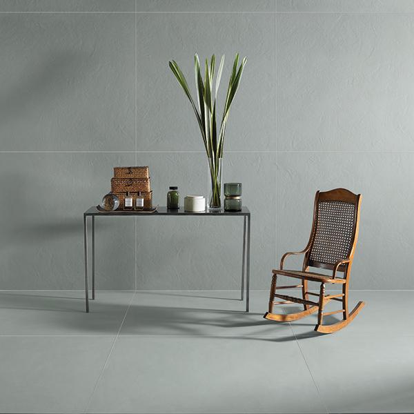 un tavolino con degli oggetti e una pianta e accanto una sedia dondolo in legno