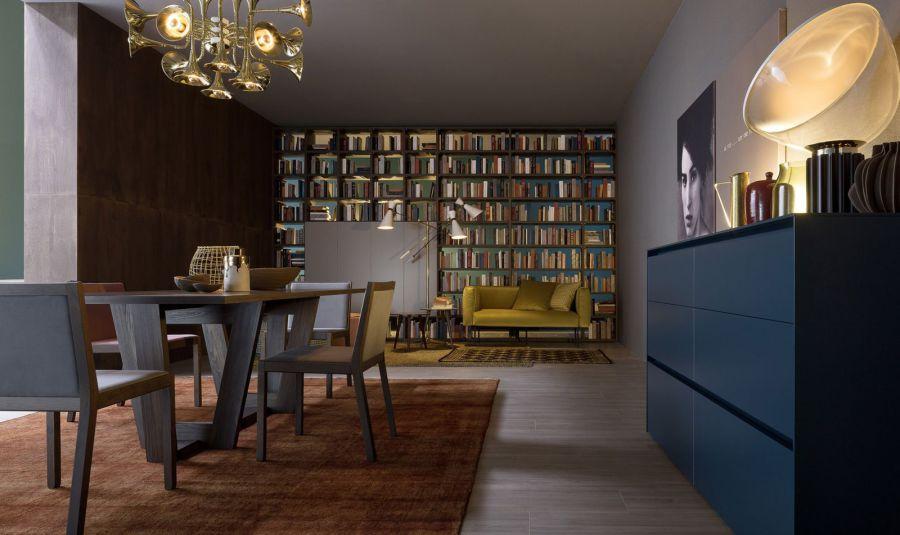 vista di una elegante sala da pranzo con un tavolo e sedie nel mezzo e una libreria in fondo alla stanza