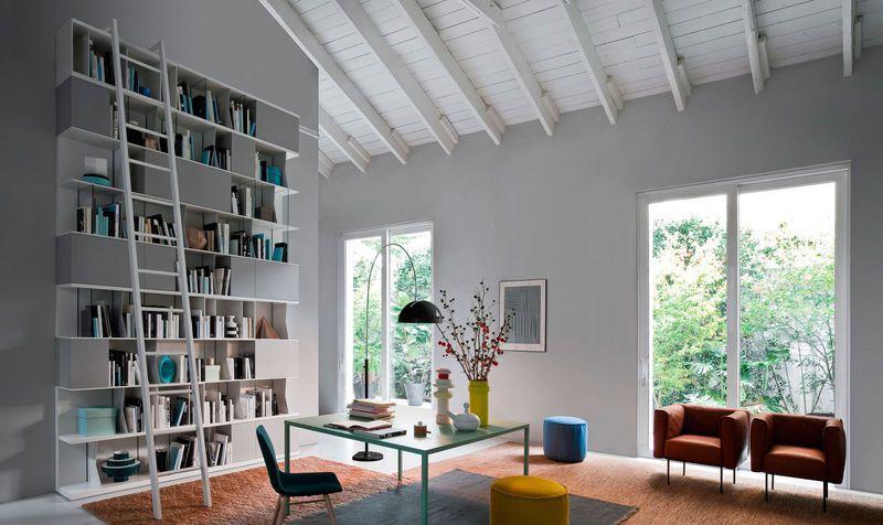 vista interna di una stanza con tavolo e sedie centrali e una libreria laterale