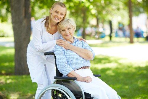 Seniorin in Rollstuhl zusammen mit Ihrer ELSNER_Pflegekraft im Grünen
