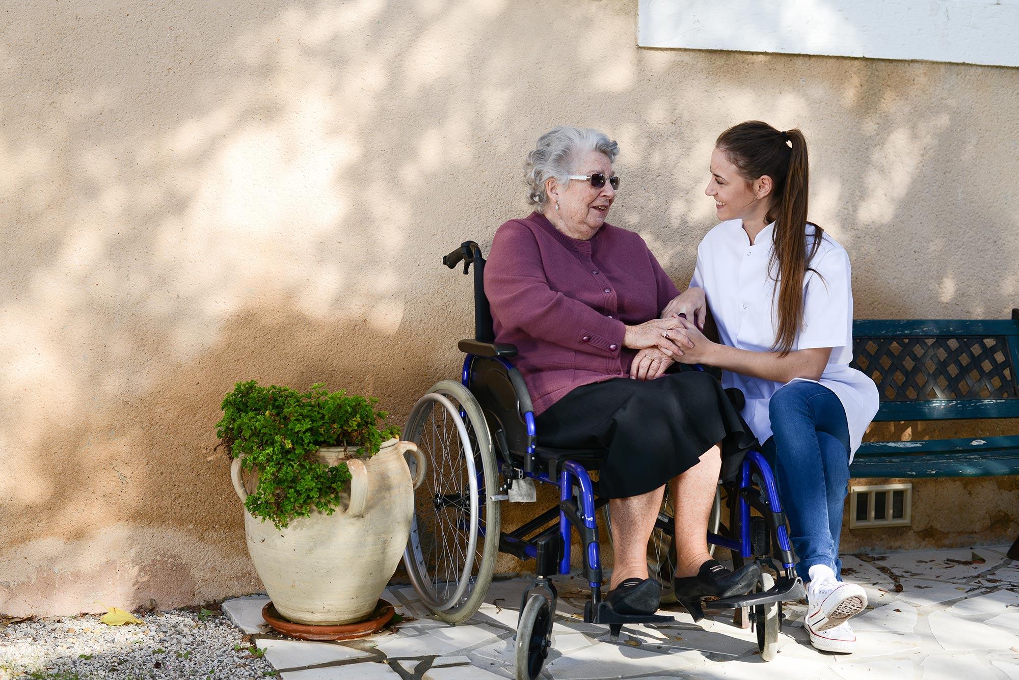 ELSNER Pflegekraft mit Seniorin auf einer Bank an der frischen Luft.