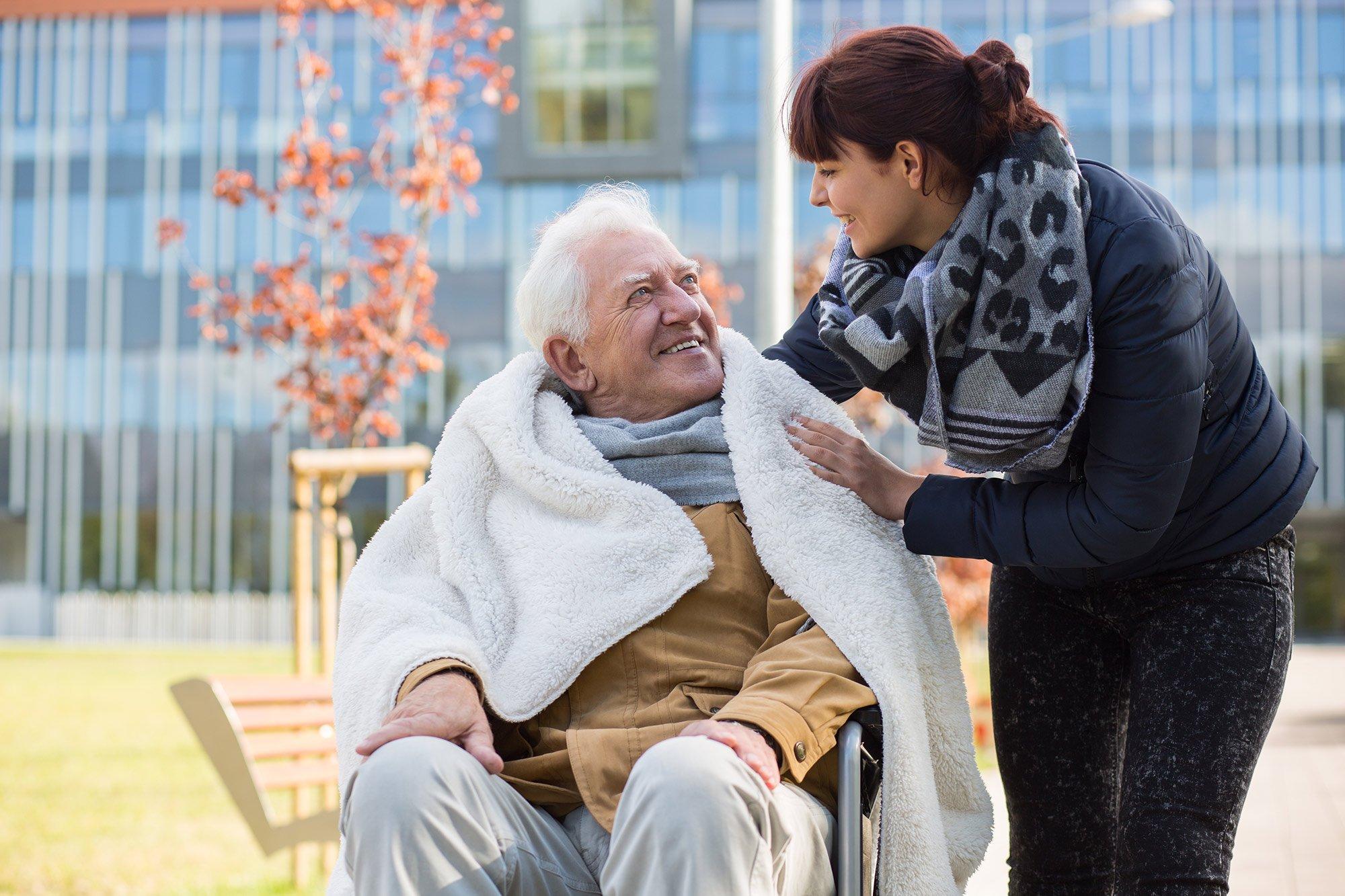 ELSNER Pflegekraft legt eine Decke um einen Senior im Rollstuhl