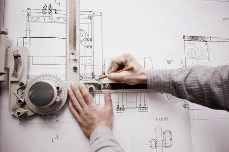 Uomo che con matita progetta un edificio