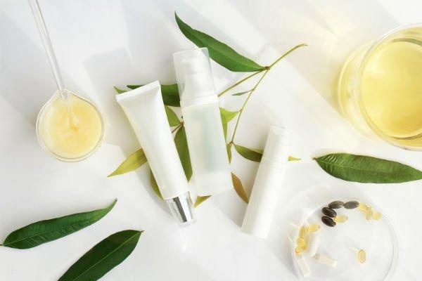 confezioni di creme viso su fondo bianco e foglie verdi