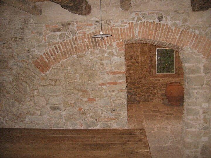 muro di pietra con arco in mattoni
