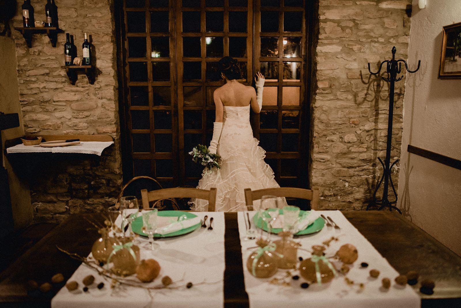 tavola imbandita con sposa che guarda dalla vetrata
