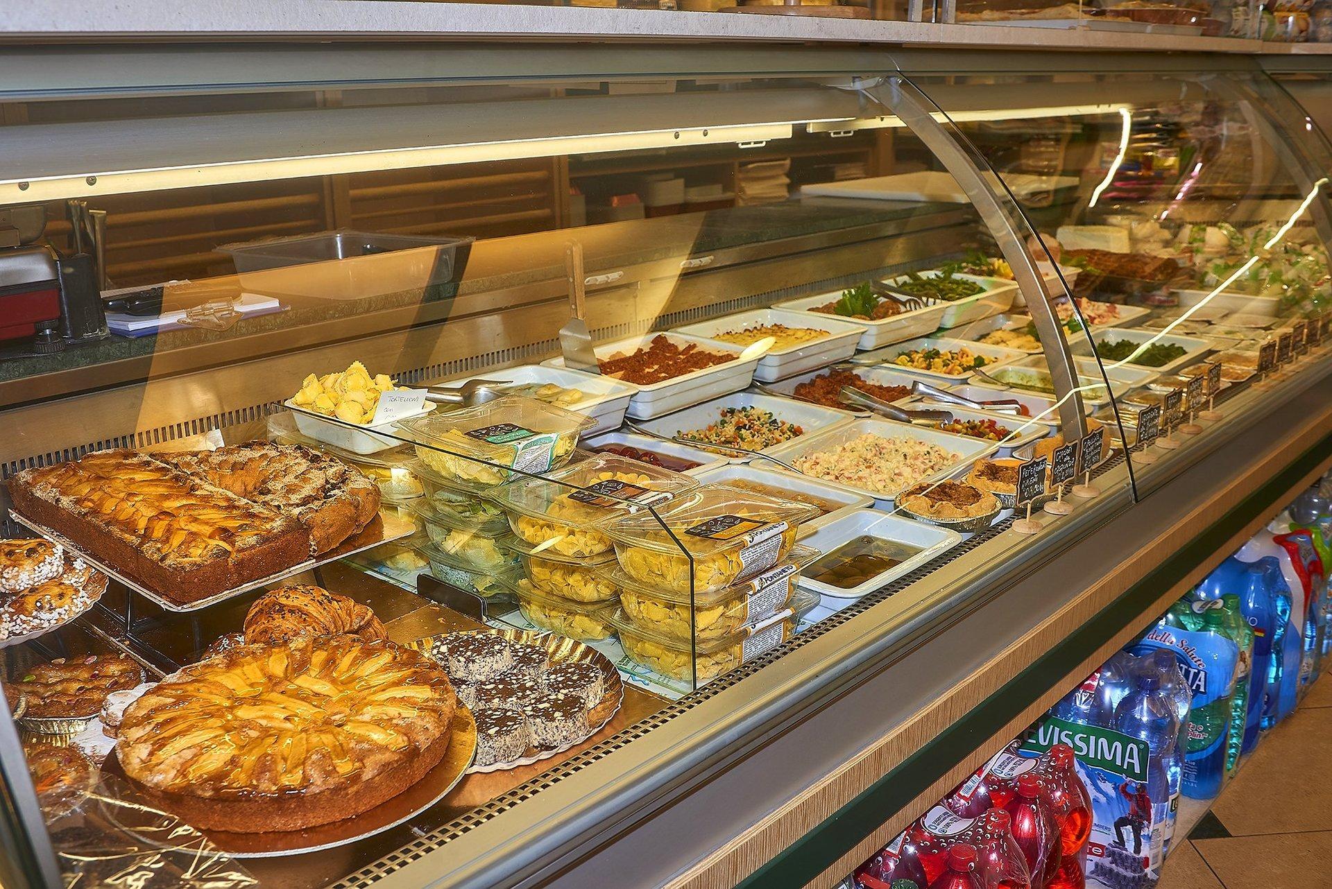 pasta, dolci, torte salate, secondi piatti ed altri prodotti alimentari nel bancone di una gastronomia