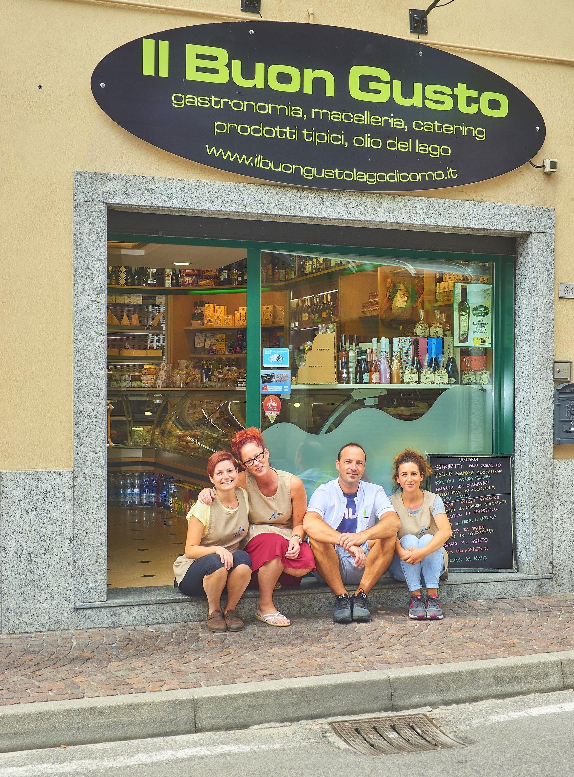 entrata della gastronomia e quattro persone sedute sullo scalino