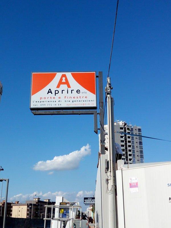 un cartello bianco e arancione con scritto Aprire porte e finestre in una citta' con vista del cielo blu