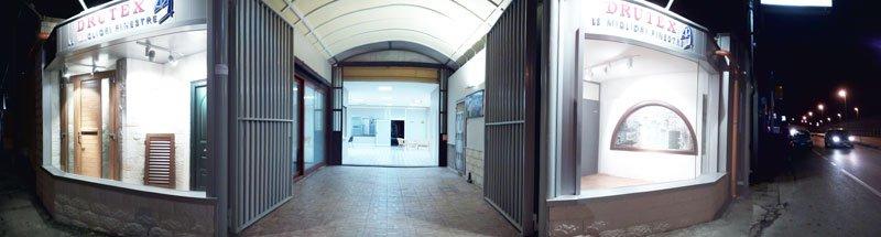 vista di un cancello d'entrata aperto con in fondo una porta e ai lati due vetrine con dei serramenti in legno esposti