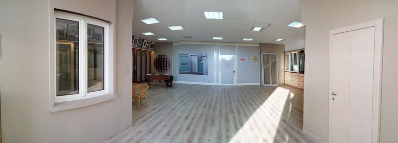 all'interno del salone, a sinistra una finestra con rifiniture in pvc di color bianco, sulla destra una porta e in fondo una sedia in paglia , un tavolo in legno e una porta di color bianco