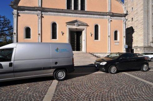 un furgone ed un auto parcheggiate davanti una chiesa