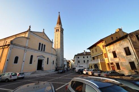vista di un piazzale con una chiesa, delle case ed un auto.