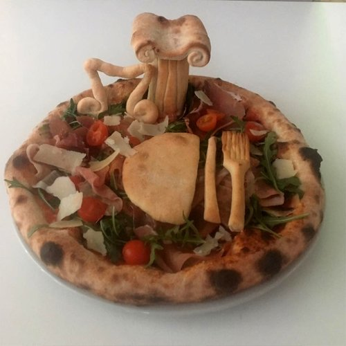 una pizza con sopra un coltello, una forchetta e una colonna fatti con l'impasto