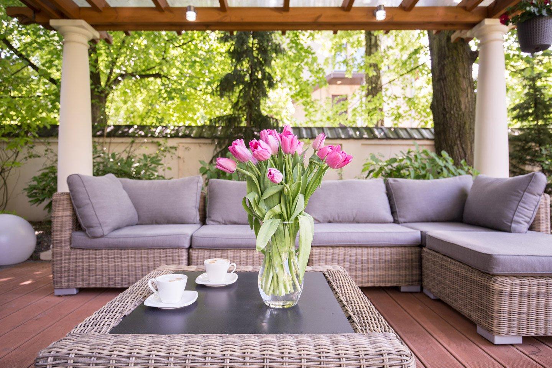 divano con tavolino vaso di fiori e tazzine da caffe