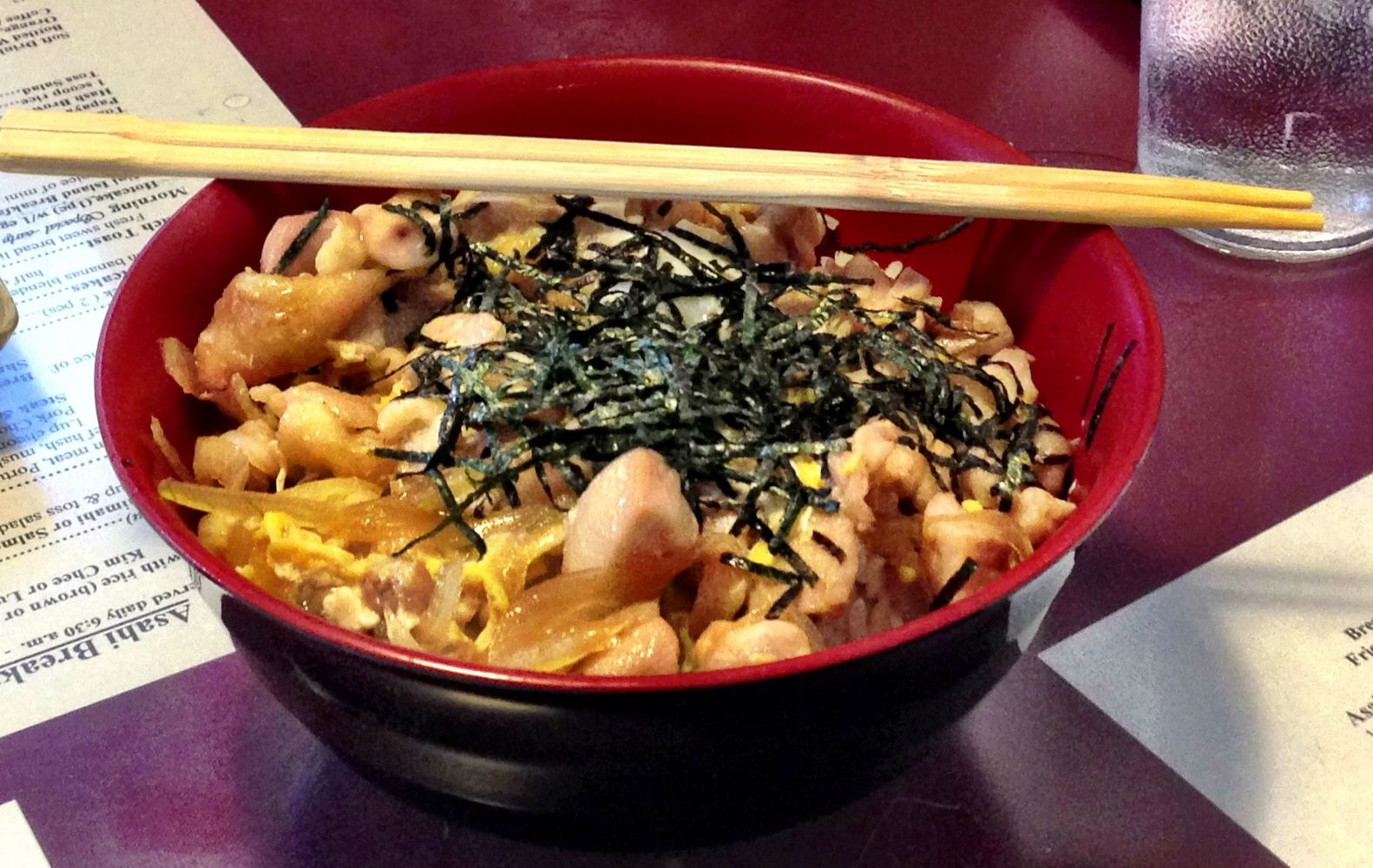 A bowl with a japanese dish and chopsticks