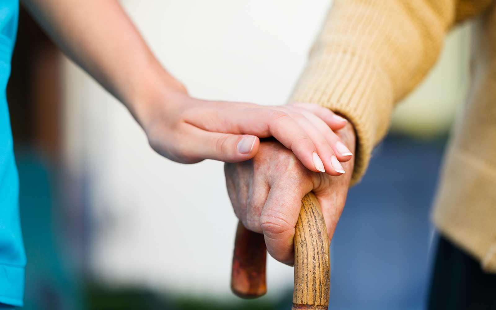una mano appoggiata su un altra di un signore con il bastone